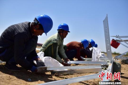 图为工人们头顶烈日进行地面铁塔组装。 云飞翔 摄